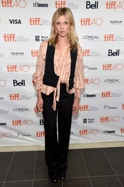 Black slacks with silver pinstripes completed Clemence Poesy's ensemble.