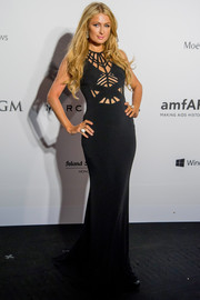 Paris Hilton sheathed her slim figure in a black gown with spiderweb peekaboo detailing on the bodice for the amfAR Hong Kong Gala.