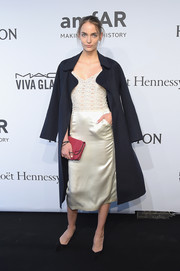 Zuzanna Bijoch accessorized with a berry-hued leather clutch for a pop of feminine color to her look.