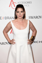 Debra Messing dressed up her plain white dress with a broad gold cuff for the 2016 ACE Awards.
