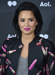 Demi Lovato perked up her beauty look with purple lipstick.