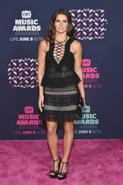 Danica Patrick put on a flirty display at the 2016 CMT Music Awards in a little black dress with a lace-up neckline and a tiered skirt.