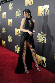 Kendall Jenner got majorly flirty at the MTV Movie Awards in a black Balmain halter dress with a strappy bodice, ruffle detailing, and a high-low hem.