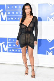 Kim Kardashian rounded out her super-sultry look with strappy black sandals by Manolo Blahnik.