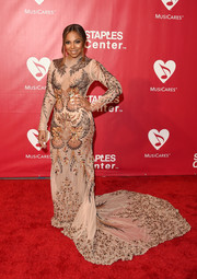Ashanti made a head-turning entrance in a curve-hugging bird-embellished gown with a long train at the MusiCares Person of the Year event.
