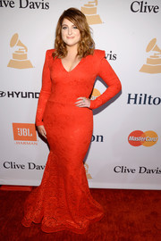 Meghan Trainor put on a curvy display in a red lace mermaid gown by Michael Costello during the Pre-Grammy Gala.