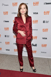 Isabelle Huppert was sleek and stylish in a raspberry-hued pantsuit during the TIFF premiere of 'Elle.'