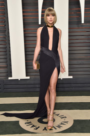 Taylor Swift unleashed her vampy side at the Vanity Fair Oscar party in a slinky black Alexandre Vauthier Couture halter gown with a navel-grazing neckline and a thigh-high slit.