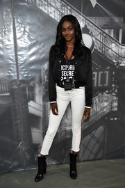 Zuri Tibby struck a pose at the 2016 Victoria's Secret fashion show photo op wearing a black track jacket over a VS shirt.