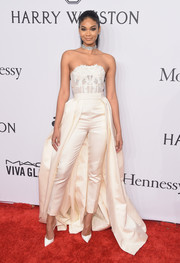Chanel Iman completed her dramatic ensemble with a pair of tapered white pants with a matching train.