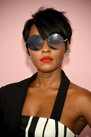 For a cool finish, Janelle Monae accessorized with oversized round shades by Karen Walker.