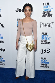 Ruth Negga rounded out her ensemble with a quilted gold cross-body bag by Saint Laurent.