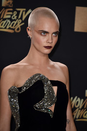 Cara Delevingne finished off her bold look with a dark red lip.