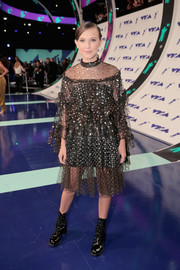 Millie Bobby Brown toughened up her cute frock with a pair of black combat boots by Stuart Weitzman.