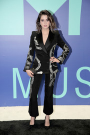 Laura Marano coordinated her suit with a black satin clutch.