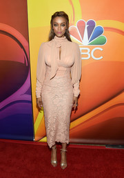 Tyra Banks paired her sexy-glam dress with gold ankle-tie sandals.