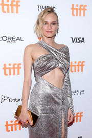 Diane Kruger matched a L'Afshar mirrored box clutch with a silver cutout dress for the TIFF premiere of 'In the Fade.'