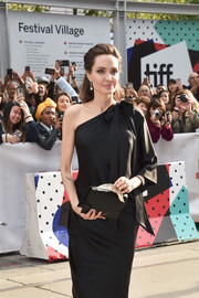 Angelina Jolie arrived for the TIFF premiere of 'First They Killed My Father' carrying a black Ralph & Russo envelope clutch with gold feather detail.