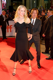 Nicole Kidman cut a shapely silhouette in a black Oscar de la Renta off-the-shoulder dress with a ruffle neckline and hem at the TIFF premiere of 'The Upside.'