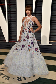 Jackie Cruz looked festive at the Vanity Fair Oscar party in a voluminous Rami Kadi gown boasting a cleavage-flaunting neckline, a feathered hem, and whimsical embellishments.