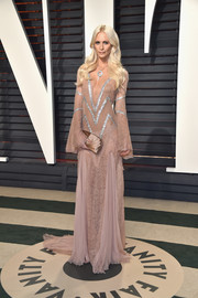 Poppy Delevingne complemented her dress with a gold satin clutch.