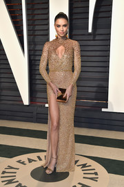 Adriana Lima flashed some cleavage and leg in a beaded gold cutout gown by Labourjoisie at the Vanity Fair Oscar party.