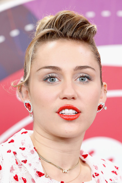 Miley Cyrus completed her accessories with a gold chain choker adorned with her initials.