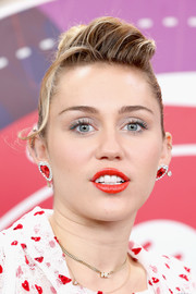 Miley Cyrus matched her outfit with a pair of huge heart studs.