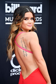 Maren Morris displayed her tattoo when she wore this backless dress to the 2018 Billboard Music Awards. It reads, 'It's a wondrous world of ridiculous things but nothing so rare as the love that it brings.'