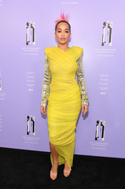Rita Ora cut a striking figure at the 2018 Fragrance Foundation Awards in a ruched lemon-yellow Tom Ford dress with bold shoulders and mirrored sleeves.