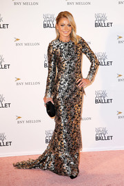 Kelly Ripa paired her dress with a woven black clutch.