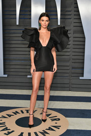 Kendall Jenner polished off her head-turning look with black ankle-strap pumps by Christian Louboutin.