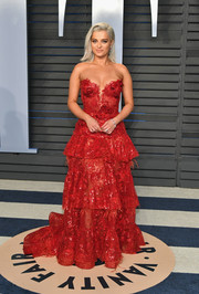 Bebe Rexha went ultra feminine in a red NEDO by Nedret Taciroglu gown, featuring a fitted, strapless bodice and a voluminous, tiered skirt, at the 2018 Vanity Fair Oscar party.