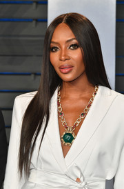 Naomi Campbell jazzed up her white suit with an oversized pendant necklace by Bulgari.