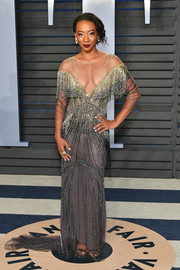 Betty Gabriel worked an Old Hollywood vibe in a fringed gray and gold gown by Pamella Roland at the 2018 Vanity Fair Oscar party.