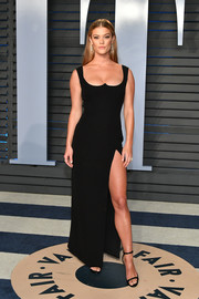 Nina Agdal flaunted her leg and cleavage in a high-slit black gown with a reverse-sweetheart neckline at the 2018 Vanity Fair Oscar party.