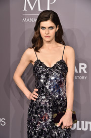 Alexandra Daddario attended the 2018 amfAR Gala New York carrying a purple Ferragamo velvet clutch with gold hardware.