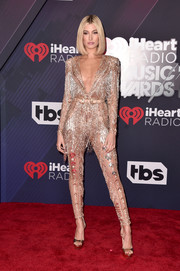 Hailey Baldwin looked absolutely dazzling in a heavily embellished rose-gold jumpsuit by Zuhair Murad Couture at the 2018 iHeartRadio Music Awards.
