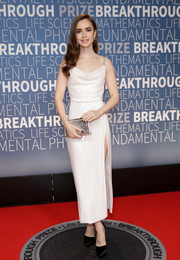 Lily Collins polished off her look with a metallic silver clutch.