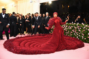 Cardi B made a show-stopping arrival at the 2019 Met Gala in a massive quilted and feathered gown by Thom Browne.