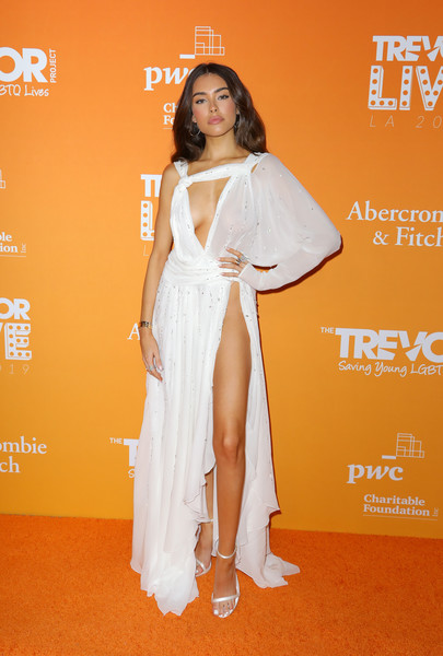 Madison Beer sent temperatures rising in an asymmetrical white Redemption Couture gown with a cleavage-baring cutout and a hip-high slit at the 2019 TrevorLIVE Los Angeles Gala.