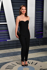 A satin clutch with gold hardware completed Natalie Portman's all-black look.