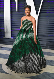 Tiffany Haddish attended the 2019 Vanity Fair Oscar party wearing a strapless Rami Kadi gown with a voluminous feathered skirt.