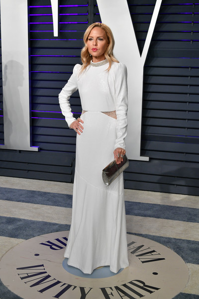Rachel Zoe attended the 2019 Vanity Fair Oscar party wearing a long-sleeve white gown with sheer cutouts.