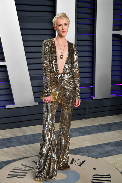 Jena Malone caught eyes in a gold sequined jumpsuit with a plunging neckline and a flared hem at the 2019 Vanity Fair Oscar party.