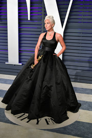 Lady Gaga teamed a black Brandon Maxwell ballgown with the perfect accessory, her Oscar statue, for the Vanity Fair after-party.