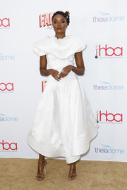 Kiki Layne paired her frock with nude ankle-strap sandals by Stuart Weitzman.