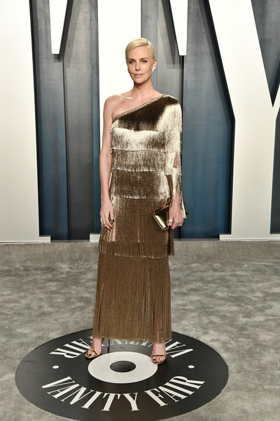 Charlize Theron looked ultra glam in a fringed gold one-shoulder gown by Dior Couture at the 2020 Vanity Fair Oscar party.