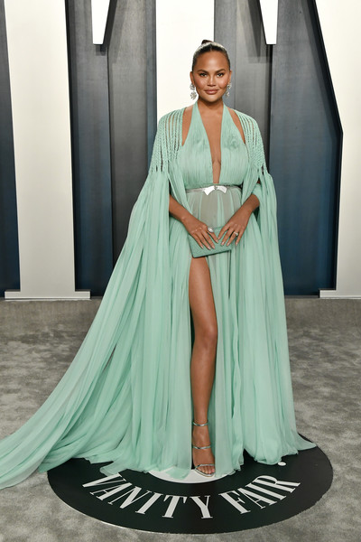 Chrissy Teigen was a standout in a caped mint-green gown by Georges Hobeika Couture at the 2020 Vanity Fair Oscar party.