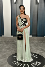 Tessa Thompson teamed her dress with a black box purse by Versace.